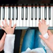 Woman teaching little girl to play the piano. Top view. — Stock Photo #73382643