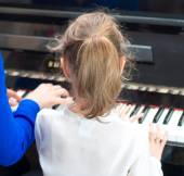 Woman teaching little girl to play the piano. Back view. — Stock Photo
