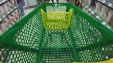 Se promener dans la boutique avec chariot vert. Mouvement rapide. 4k. — Vidéo