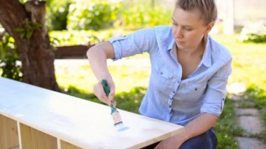 Woman with brush painting wooden furniture. — Stock Video