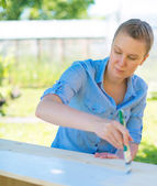 Woman with brush painting wooden furniture. — Stock Photo