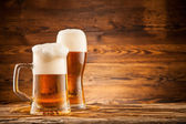 Glasses of beer on wooden planks — Stock Photo