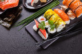 Delicious sushi pieces served on black stone — Stock Photo