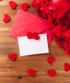 Envelope with roses on wooden table — Stock Photo