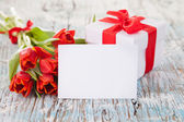 Red tulips with gift on wooden planks — Stock Photo
