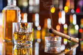 Whiskey drink with smoking cigar on bar — 图库照片
