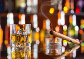 Whiskey drink with smoking cigar on bar — Stock Photo