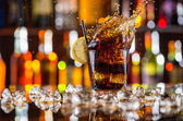 Glass of cola drink with splash on bar counter — Stock Photo