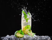 Mojito drink with splash on black background — Stock Photo