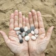 Stonesin female hands on a background of sand. — Stock Photo #52661909