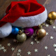 Christmas balls and Santa hat on wood background — Stock Photo #60974279