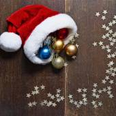 Christmas balls and Santa hat on wood background — Stock Photo