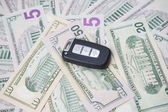 Car key on a background of dollars — Stock Photo