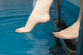 Beautiful female feet on the steps of the pool — Stock Photo