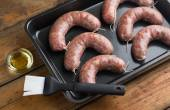 Raw homemade sausages in a pan — Stock Photo