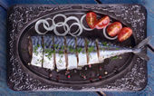 Salted mackerel with vegetables on a plate, top view — Stock Photo