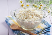 Cottage cheese in a glass container, a wooden spoon and chamomil — Stock Photo