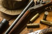 Hunting rifle, ammunition, a knife and a cap on the table — Stock Photo