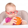 Little child sitting in a chair and plays with orange fruit — Stock Photo #58714117