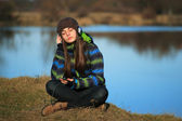 Young girl sitting on the ground and listening  music after hike — Stock Photo