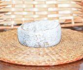Fresh goat cheese ripened in ash on the straw — Stock Photo