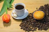 Cupcake on the heap of coffee beans and a cup of fresh coffee — Stock Photo
