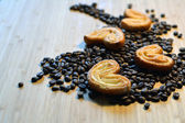 Sugary biscuits on coffee beans — Stock Photo