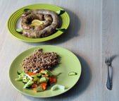 Homemade pork sausage served with garnish of boiled buckwheat wi — Stock Photo