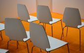 White plastic chairs over orange floor in a conference room — Stock Photo