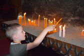 A boy lits a candle in a church — Stockfoto