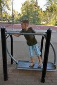 A boy exercising on outdoor equipmnent — Stock Photo