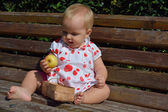 A baby girl is examining an apple  — Stock Photo