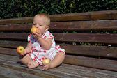 A girl eats apples sitting on the bench — Stock Photo