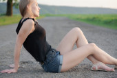 Beautiful model sitting on the road — Stock Photo