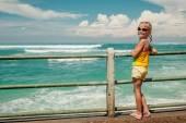Szczęśliwa dziewczynka stojący przy plaży w czasie dnia — Zdjęcie stockowe