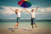 Happy couple jumping on the beach at the day time — Stock Photo