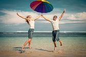 Coppia felice saltando sulla spiaggia a tempo di giorno — Foto Stock