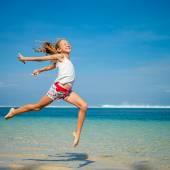 Dospívající dívka, která skočila na pláži v modré moře pobřeží v létě vaca — Stock fotografie