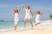 Happy family jumping on the beach on the day time — Stock Photo