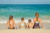 Happy family sitting on the beach at the day time — Stock Photo