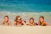 Happy family lying on the beach at the day time — Stock Photo