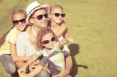 Retrato de uma família feliz sentado na grama na hora do dia — Fotografia Stock