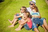 Portrait a happy family sitting on the grass at the day time — Stock Photo