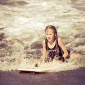 Happy teen girl with surfboard  on beach at the day time — Stock Photo