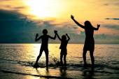Silhouette of happy family who playing on the beach at the sunse — Stock Photo