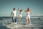 Família feliz brincando na praia na hora do dia — Fotografia Stock