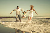 Happy family playing on the beach at the day time — ストック写真