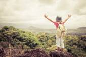 Little girl with a backpack standing on a mountain top — Stock Photo