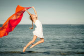Teen girl jumping on the beach at the day time — Stock Photo