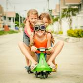 Three happy children playing on the road at the day time — Stock Photo
